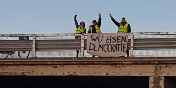 Three Dutch yellow vests holding up a sign demanding democracy