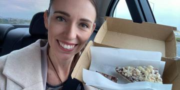 Jacinda Ardern smiling in the camera, posing with a piece of pie.