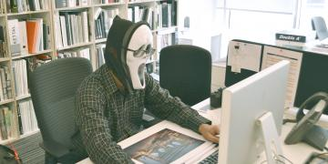 Masked man sitting behind a desk, using a computer