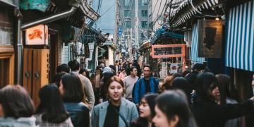 people walking between korean houses