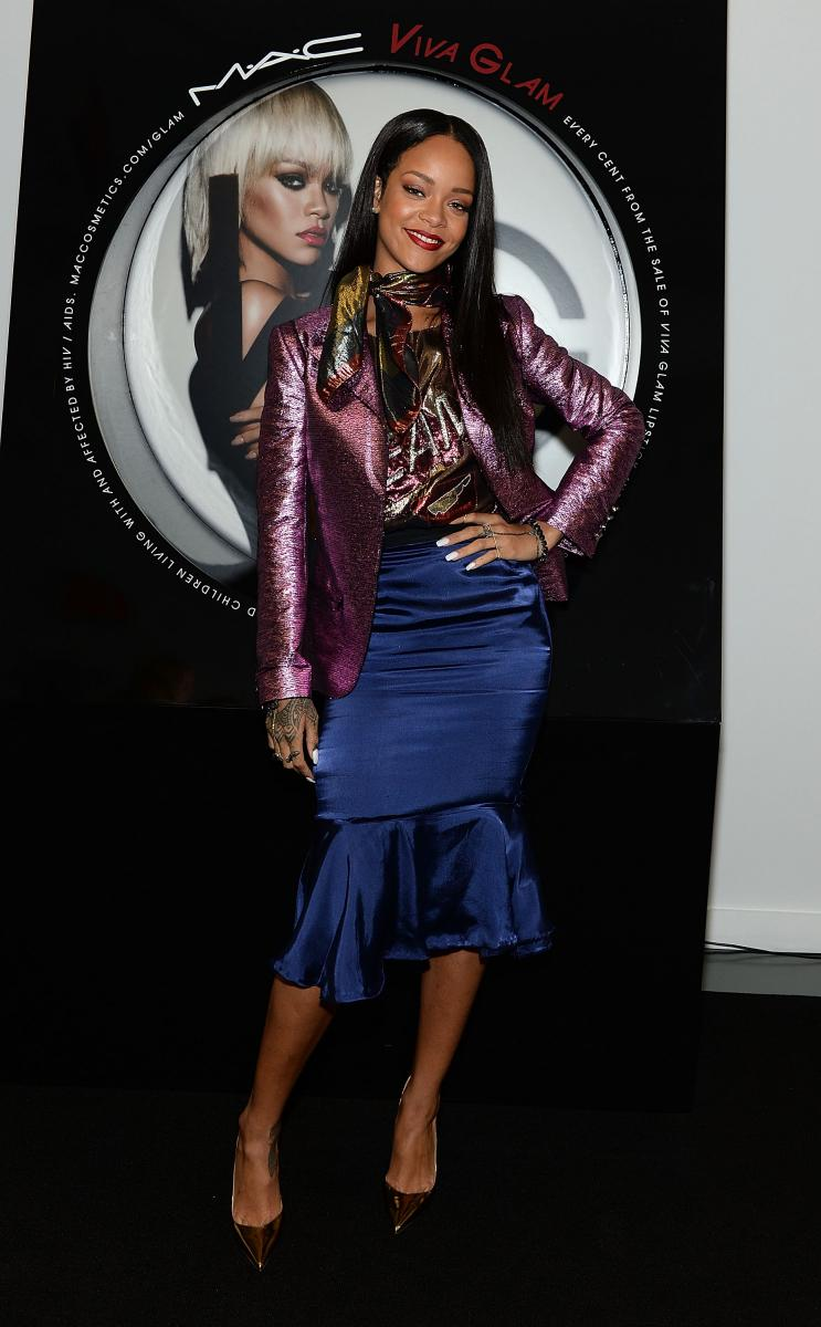 Rihanna posing next to her image advertising MAC Viva glam products